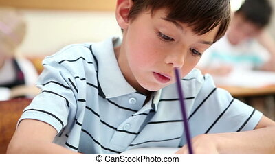 Pupil writing on his notebook in the classroom