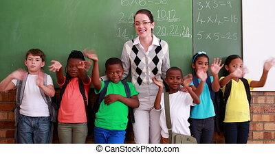 Pupils and teacher waving at camera