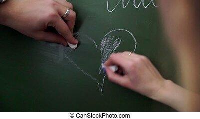 Pupils in school draw heart at chalk Board