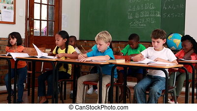Pupils listening and writing during class in elementary...