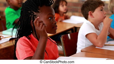 Pupils listening attentively during class in elementary...