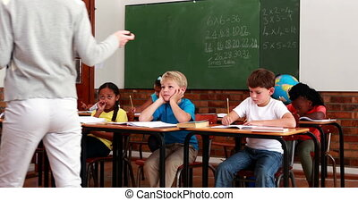 Pupils listening to teacher during class in elementary...