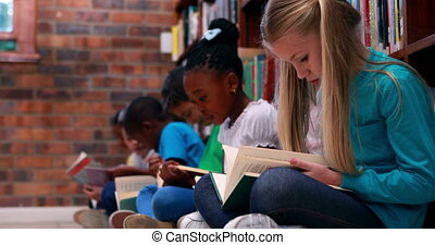 Pupils sitting in a row reading in the library in elementary...