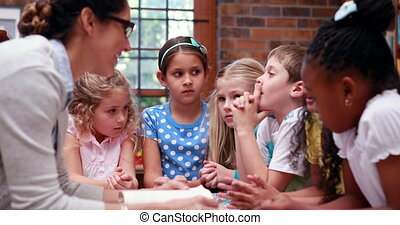 Pupils talking with their teacher in the library in elementary school