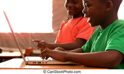 Pupils using laptop in classroom