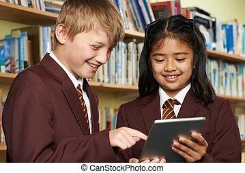 Pupils Wearing School Uniform Using Digital Tablet In Library