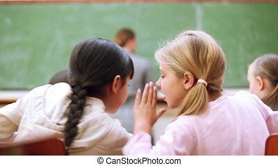 Pupils whispering secrets in the classroom