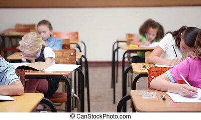 Pupils sitting at desks are working in a classroom