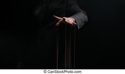 Puppet Master controls and manipulates the puppets with strings attached to his fingers. The hand of a businessman in a suit close up controls the destinies of people. Manipulation, addiction concept. Isolated on black background. Slow motion.