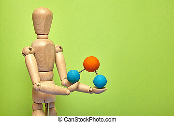 Wooden puppet with molecule on green background