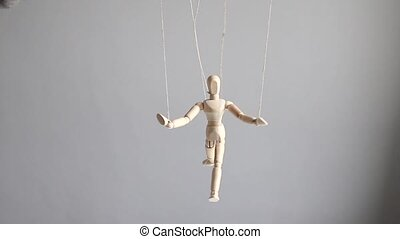 Human wood figure with threads suspended in the air on gray background. Manipulation, addiction concept.