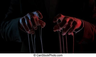 Puppeteer manipulating and pulling strings of marionettes. Male hands close up painted with colored lights on black background. People are toys in hands of dominant businessman dictator. Slow motion