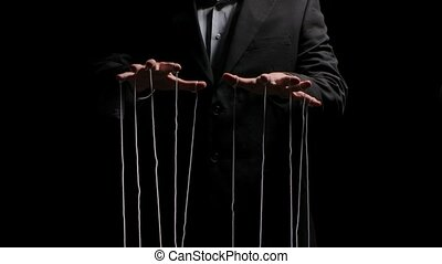 Puppeteer pulls the doll strings tied to his fingers. Puppet rope manipulation concept and control hand. Businessman controls the mind and actions of people. Isolated on black background. Close up. Slow motion