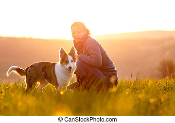 Puppy dog and woman on sunset or sunrise, dog walk at the morning