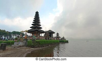 Tourists visit the beautiful, Pura Ulun Danu Bratan, a lakeside, Hindu temple with tiered pagodas and landscaped gardens in Bali Indonsia.