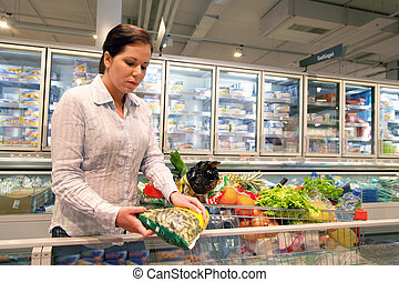 Young woman buys in the supermarket food and fruit.