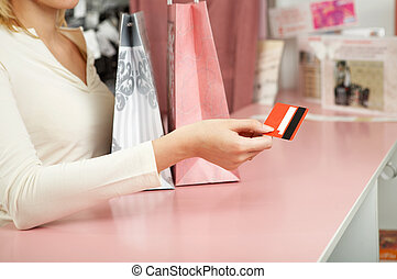 Purchase - The hand holds a credit card against a counter