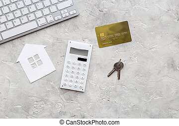 purchasing house with online card payment on work desk stone background top view