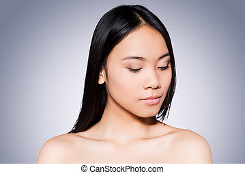 Pure beauty. Portrait of beautiful young and shirtless Asian woman looking down while standing against grey background