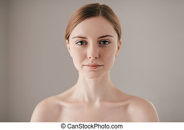 Pure beauty. Portrait of redhead woman with freckles looking at camera while standing against grey background