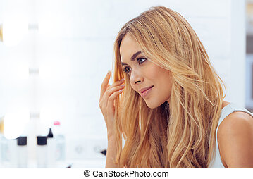 Pure beauty. Side view of beautiful young woman looking at her reflection in mirror while sitting at the dressing table