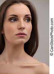 Pure beauty. Thoughtful young shirtless woman looking away while isolated on grey background