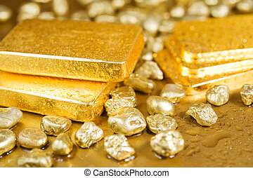 pure gold - fine gold ingots and nuggets on a wet golden...