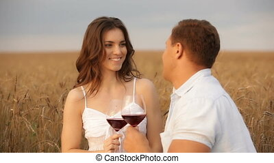 Young people having a rural date drinking wine and kissing