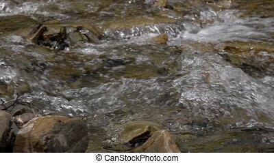 Pure stream of mountain river among stony coasts. Slow motion