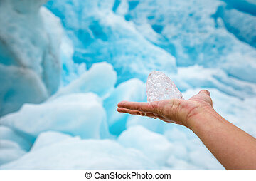 Pure transparent piece of ice in hand with the Svartisen glacier, Norway