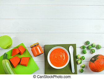 Puree from pumpkin in the plate and jar on white wooden background