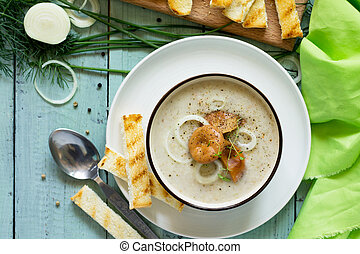 Puree soup mushrooms with croutons in a bowl on a kitchen wooden table. The concept of healthy eating.  Diet menu. Top view with copy space.