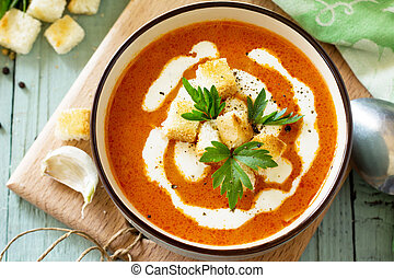 Puree soup tomato with croutons and cream in a bowl close-up on a kitchen wooden table. Diet menu. The concept of healthy eating.