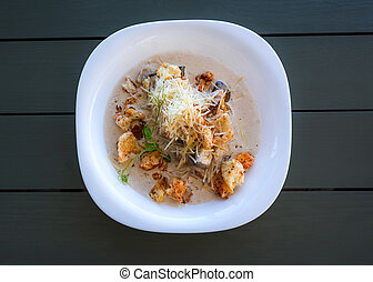 Puree soup with cheese and mushrooms. Hot soup with croutons and grated cheese on a white plate top view