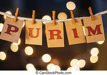 The word PURIM printed on clothespin clipped cards in front of defocused glowing lights.