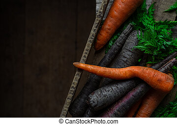 Purple and orange carrots in wooden crate, top view