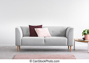 Purple and pastel pink pillow on the grey comfortable couch in bright living room interior with pink carpet and coffee table, real photo with copy space on the empty white wall