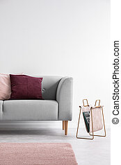 Purple and pastel pink pillow on the grey couch in bright living room interior, real photo with copy space on the empty white wall