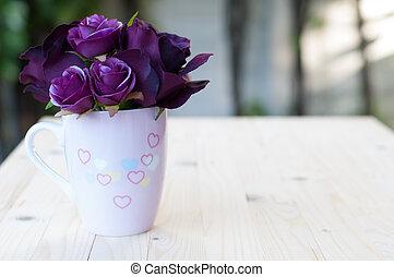 Purple artificial rose in cup.