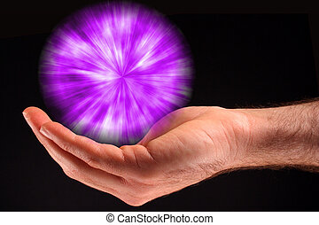 A hand holding a purple ball of light against a black background.