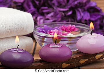 purple candles and flowers in spa setting - three purple ...