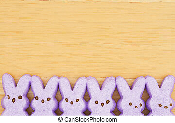 Purple candy bunnies on textured wood background