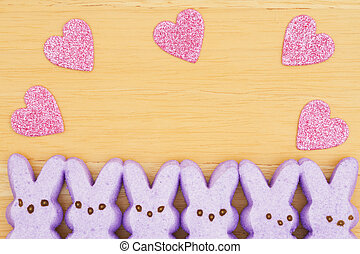 Purple candy bunnies with pink hearts on textured wood background