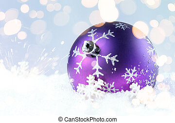 Purple christmas ball on a blue sparkle background.