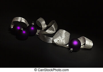 Purple Christmas balls and white ribbon on black background