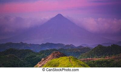 purple dense clouds surround Mayon Volcano silhouette - ...