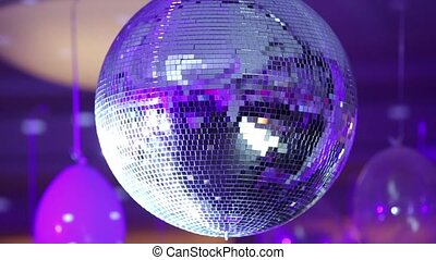 Purple disco ball reflecting the rays into the background of balloons. Close up