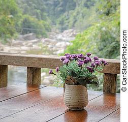 Purple flower on wooden table