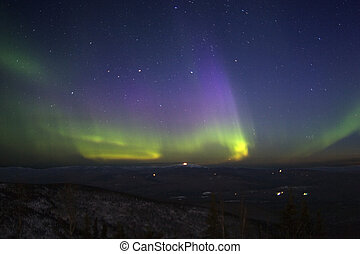 Purple-green-yellowish northern lights in starry sky over hill terrain litted with moonlight. April 2006, near Fairbanks, AK.