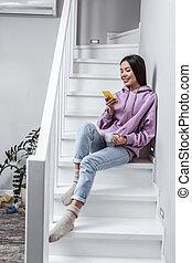 Slim appealing woman wearing jeans and purple hoodie sitting on stairs